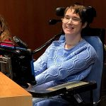 Smiling woman with short brown hair wearing glasses and a blue sweater using a wheelchair and augmentative communication device.